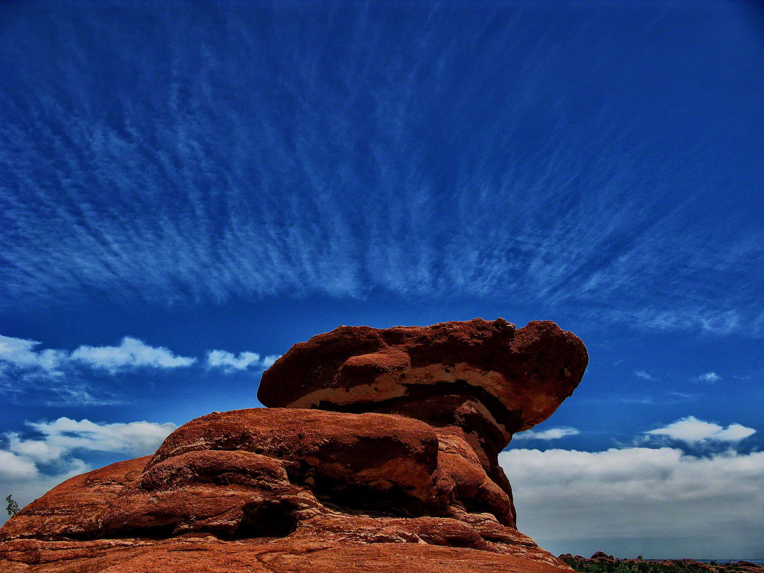 A perfect cloud formation surrounds the Scotsman Rock.